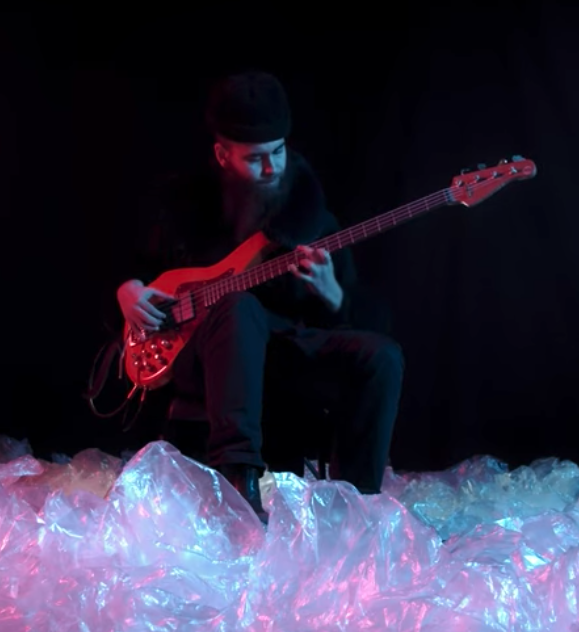 Cassius Lambert playing bass in a dark room and with the bass in his hands.