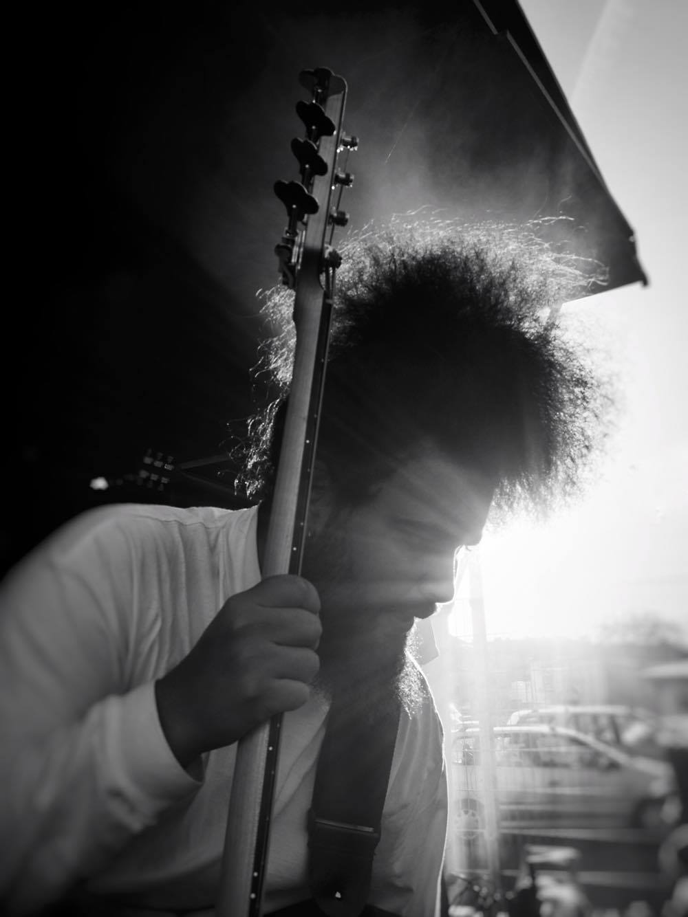 Cassius Lambert is holding his bass. Intense bright light coming from behind and in his face.