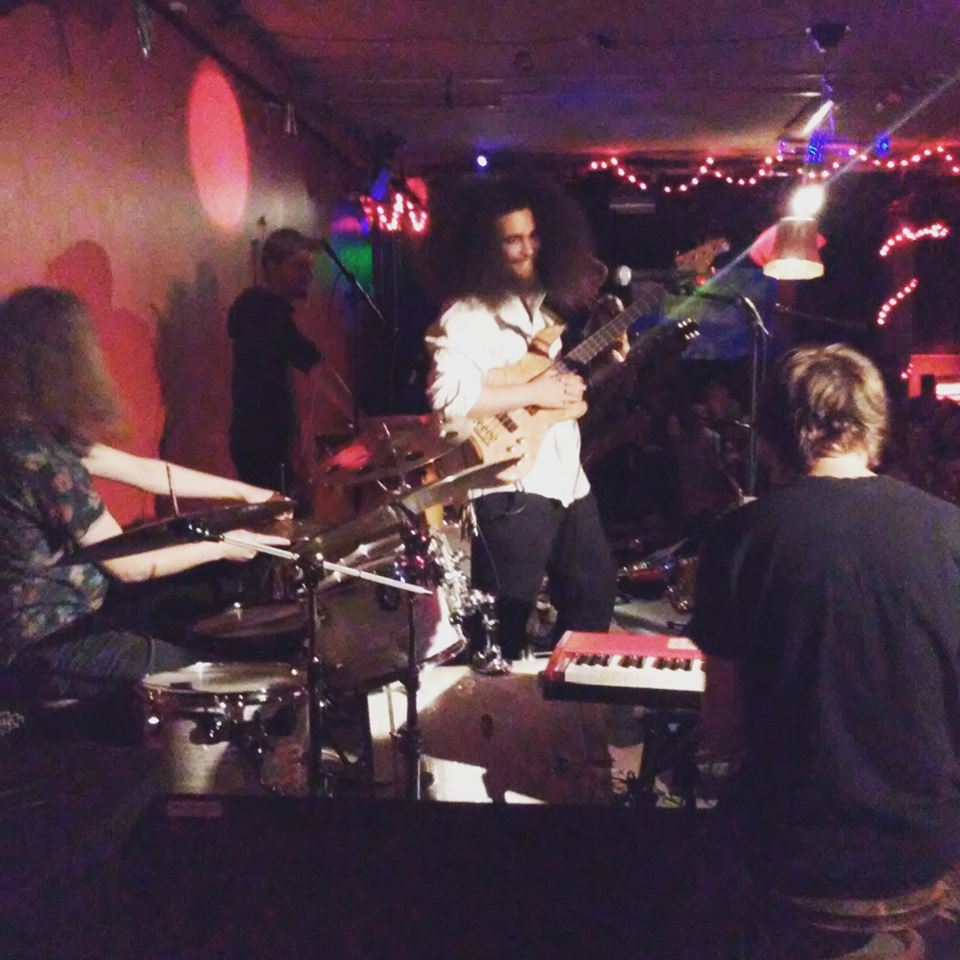 Cassius Lambert is holding his bass and smiling. Simon Flack and Markus on drums. Johan on keys. Lamps in many colors.