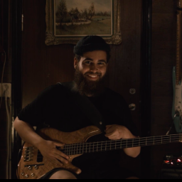 Cassius Lambert has his bass in his arms and is smiling